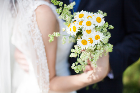 Beautiful yellow chamomile bouquet in hands of bride and groom Stock Photo