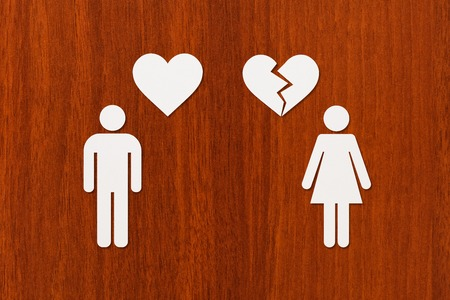 unrequited love: Paper man with heart and woman with broken one on wooden background. Unrequited love or divorce concept. Abstract conceptual image