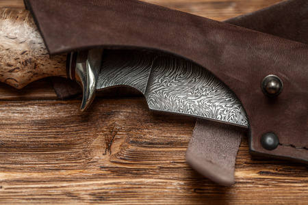 Hunting damascus steel knife handmade in sheath on a brown wooden background, closeup Stock Photo