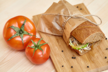 Big bread sandwich on wooden cutting board with ingridients, closeup