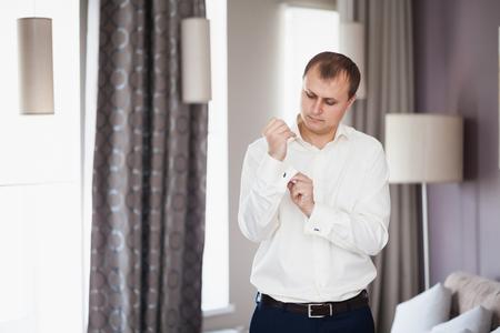 Elegant young fashion man fixing his cufflinks in hotel, wedding preparation of groom