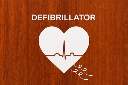 fibrillation: Heart shape with echocardiogram and DEFIBRILLATOR text. Medical cardiology concept