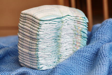 incontinence: Stack of diapers or nappies on knitted blanket, closeup