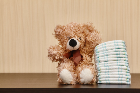 Stack of diapers or nappies with teddy bear, closeup