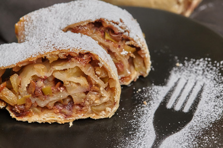Apple strudel with icing sugar and raisins on black plate, wooden background
