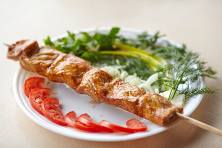 grill: Grilled pork kebab on skewer with tomatoes, onion and greens on plate