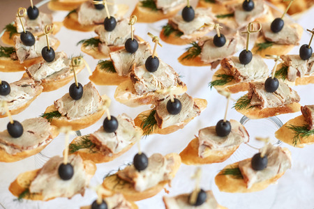 Catering of canape with olives, baguette and meat on white background