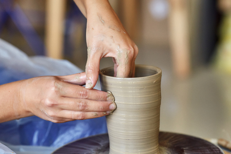 Creating a jar or vase of clay. Woman hands on potters wheel