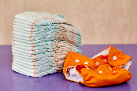 incontinence: Stack of disposable diapers or nappies on purple background and reusable one