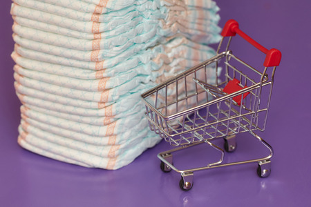 incontinence: Stack of diapers or nappies and mini shopping cart, parenthood and money concept