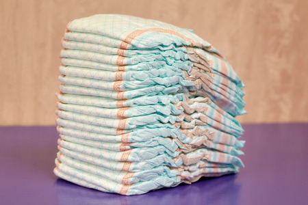 incontinence: Stack of diapers or nappies on purple background, closeup
