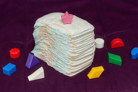 incontinence: Stack of diapers or nappies with colorful toys on purple background, closeup