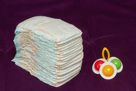 incontinence: Stack of diapers or nappies with colorful rattle on purple background, closeup