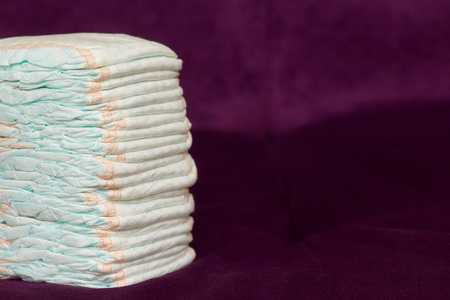 incontinence: Stack of diapers or nappies on purple background, closeup, copyspace Stock Photo