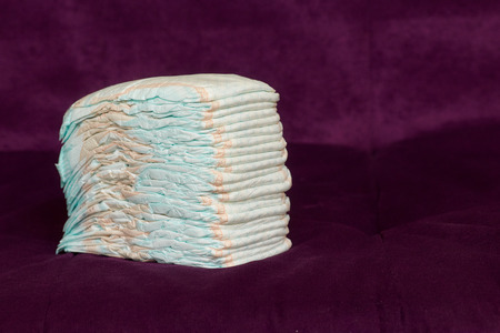 Stack of diapers or nappies on purple background, closeup, copyspace Imagens