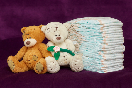 incontinence: Stack of diapers or nappies with teddy bears on purple background, closeup