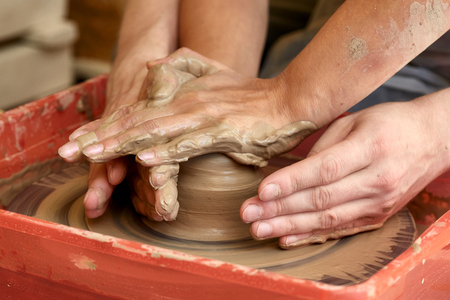 sculp: Hands of two people create pot on potters wheel. Teaching pottery, carftmans hands guiding Stock Photo