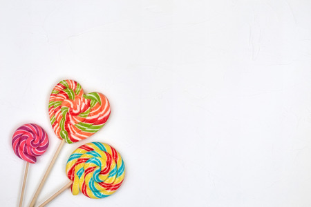 bonbons: Swirl rainbow lollipop candy on white background, copyspace