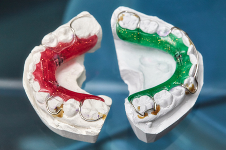 Colorful dental braces or retainers for teeth on black glass background, closeup