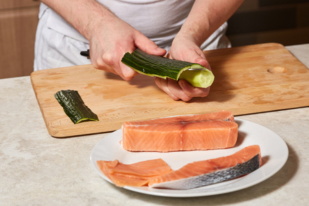 Chef making sushi rolls. Hands cutting cucumber and salmon fish
