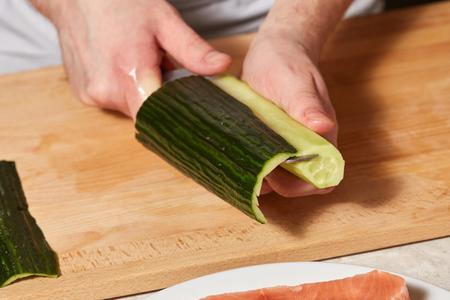 Chef making sushi rolls. Hands cutting cucumber, closeup