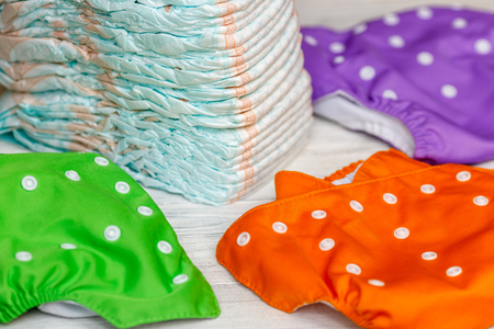 Stack of disposable diapers or nappies and colorful reusable Stock Photo