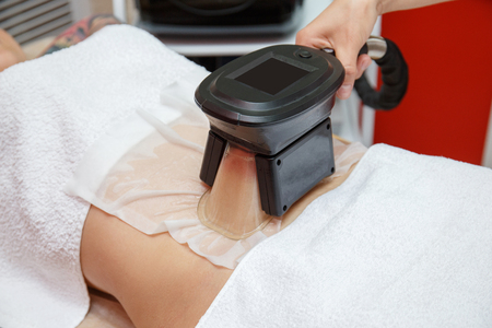 Woman getting cryolipolysis fat treatment procedure in professional cosmetic cabinet or spa center, closeup