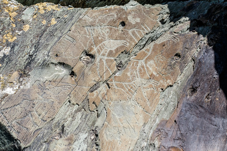 Ancient cave drawings and carving, petroglyphs on wall. Western Siberia, Russia