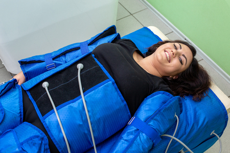 Smiling woman having procedure of anti cellulite massage on pressotherapy machine in beauty center Foto de archivo