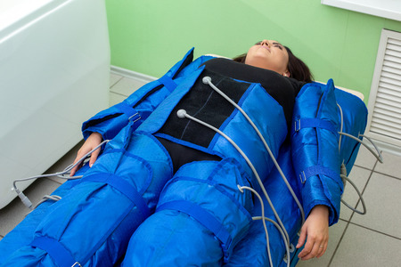 Smiling woman having procedure of anti cellulite massage on pressotherapy machine in beauty center