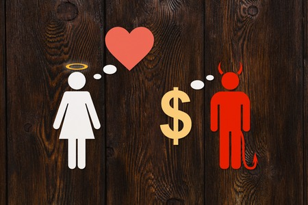 Paper couple, love vs money concept. Devil man and angel woman. Abstract conceptual image Stock Photo