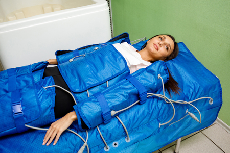 Smiling woman having procedure of anti cellulite massage on pressotherapy machine in beauty center 스톡 콘텐츠