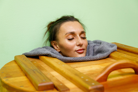 Woman having spa treatment and relaxing in wooden hot barrel sauna, cedar bathtub