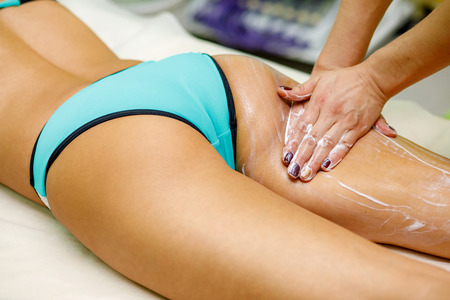 Slim beautiful woman having massage with cream on her thigh and buttocks in spa salon