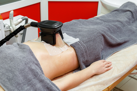Weight loss and slimming. Woman getting cryolipolysis treatment in beauty salon