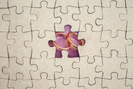 Missing jigsaw puzzle piece and wedding rings inside. Marriage concept. Abstract conceptual image