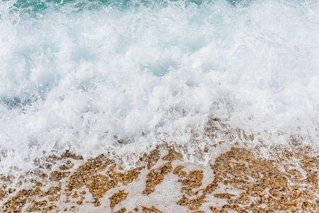 Turquoise sea waves splashing on pebble shore background Stock Photo