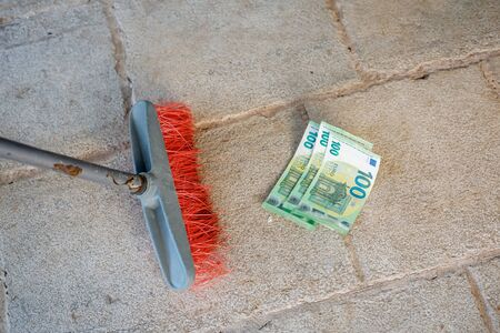 Housekeeping broom sweeping hundredth euro banknote on street. Money or business concept