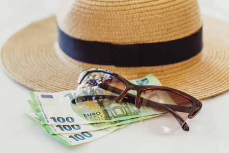 Sun hat with sunglasses and 100 hundredth euro banknotes. Money or vacation concept