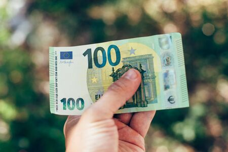 Male hand holding 100 hundredth euro banknote on green background outdoors, closeup