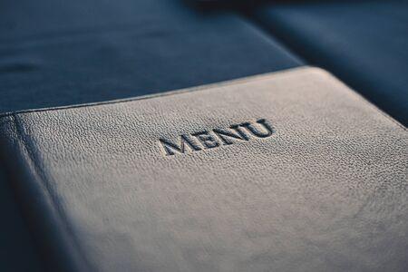 Dark blue menu book on table in restaurant, selective focus closeup