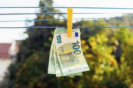 Euro banknotes hanging with clothespin on clothesline. Money laundering business concept. Abstract conceptual image