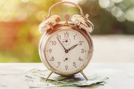 Old and rusty alarm clock and 100 hundredth euro banknotes. Business or time and money concept