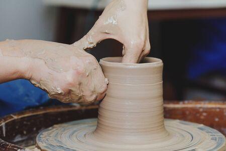 Mains de femme sur le tour de potier, potier au travail. Artisan artiste façonne le pot