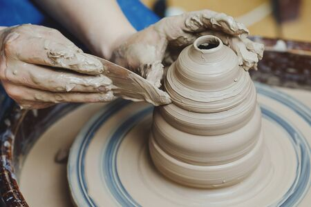 Woman hands on pottery wheel, potter at work. Craftsman artist shapes pot