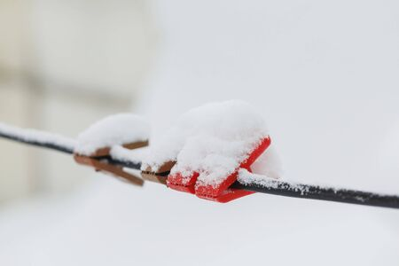 Colorful clothespins on clothesline covered with snow outdoors. Winter scene, housework concept