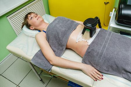 Woman getting cryolipolysis fat treatment procedure in beauty salon