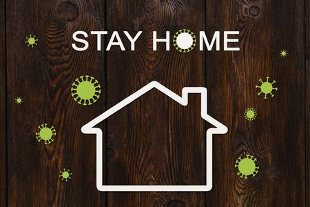 Coronavirus or covid19 quarantine. Stay home concept. Paper white house and virus outside on wooden background Stock Photo