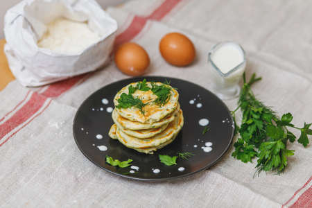 Plate with stack of fresh fried pancakes and ingridients on table, closeup