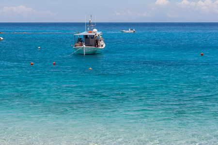 Small Boat in the Blue waters of Ionian sea, near Agios Nikitas village, lefkada Stock Photo